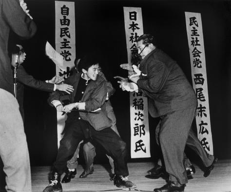 Otoya Yamaguchi, a right-wing student, assassinates Inejiro Asanuma, Socialist Party Chairman, during his speech at the Hibiya Hall in Tokyo. Yasushi Nagao.