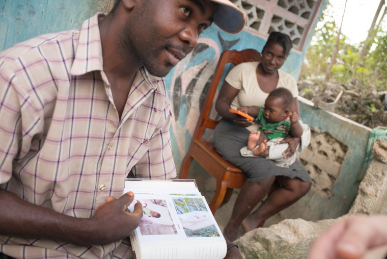 Jean Phillipe Saintellus talking about his family photo album, with his wife Manushka and 4 month old child Wenshel. Bois Jolie, Haiti. January, 2015. [photo:Pradip Malde]
