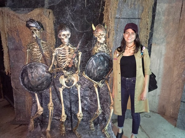Peggy standing next to some skeletons at disturbia screams in the park