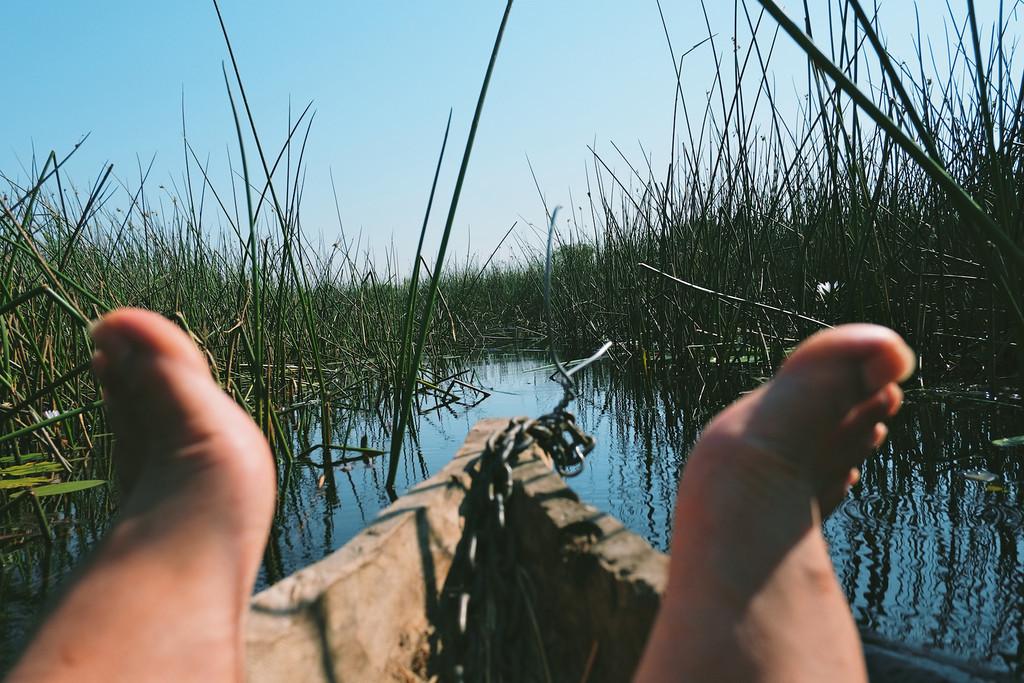 feet on a canoe, makoro, okavango delta, botswana, africa