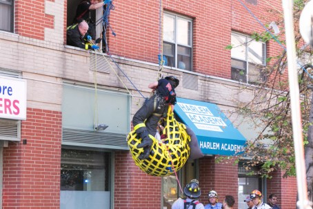 note: fire captain asked that her face not be shown-- A woman weighing over 750lbs is extracted from her apartment through a window above 5th avenue by the FDNY and paramedics. (Photo Jennifer L Gonzeles)