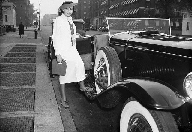 "A smiling, Marva Trotter ""the most beautiful woman in Harlem"" steps into her Duesenberg in Harlem, 1940's."