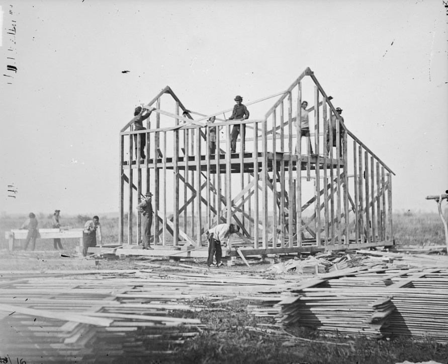 "Ten men building a balloon frame house, Omaha Reservation, Nebraska, 1877. Note the wall studs go all the way up to the roof. The floor joists attach to a ""sole plate"" supported by the foundation piers. The attic floor joists are supported by a ""ribbon"" or ledger board attached to the inside surfaces of the side wall studs. The diagonals are temporary supports. A stack of siding or floorboards is in the foreground."
