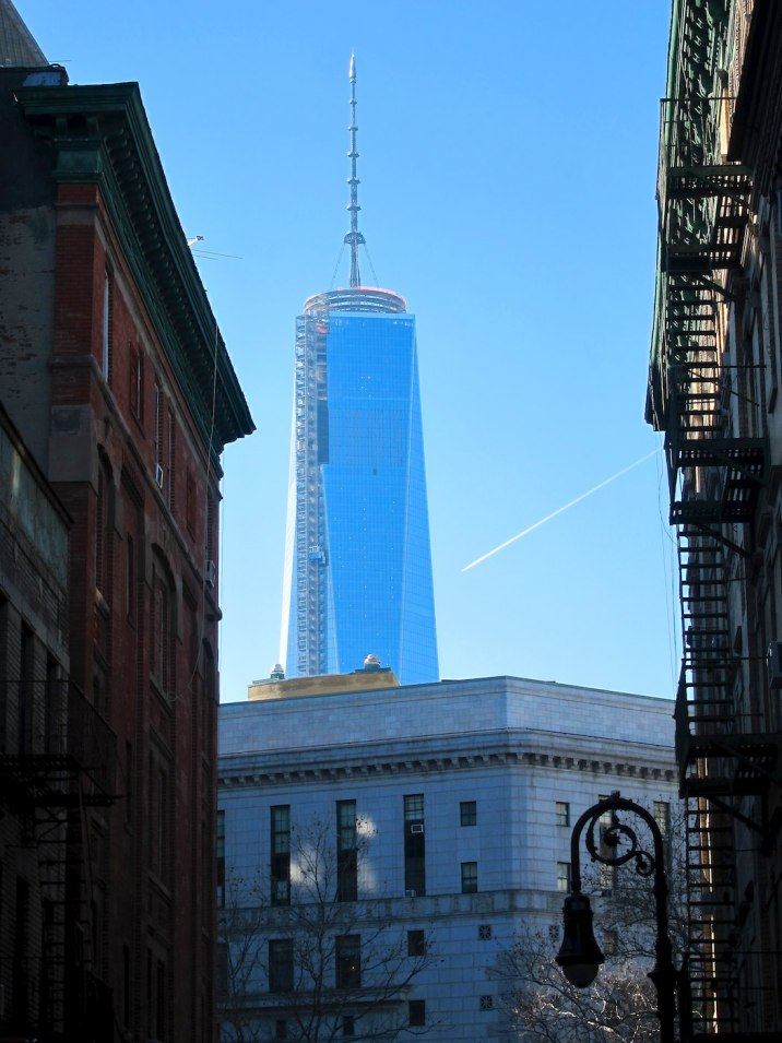 Freedom Tower and the condensation trail of a jet plane.