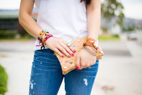 An Dyer wearing Rich & Skinny Clinton Ankle Peg Jeans, Sole Society Oversized Turquoise Ring, ShopLately Glint & Gleam Neon Necklace & multicolor Cork Clutch, Kim & Zozi Bracelets, La mer Collections Watch