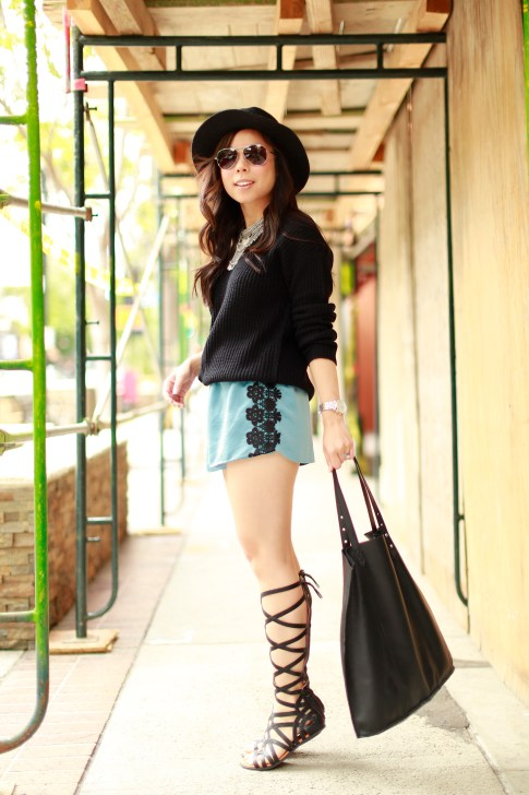 An Dyer tiptoeing in Gladiator Sandals, Delikate Rayne Shorts with black fedora panama hat, fisherman sweater