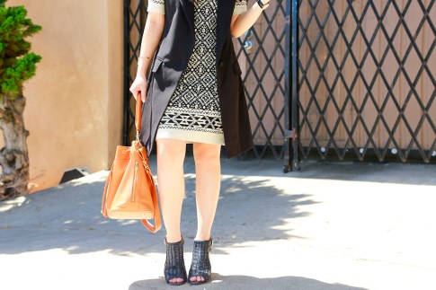 An Dyer wearing Karen Kane dress with Louise et Cie Sheree Woven Leather Sandals and Ora Delphine Bucket Bag and Express Vest Coat