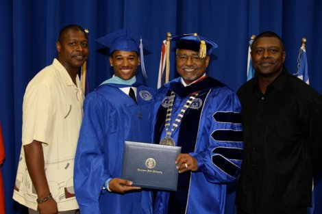 Franz receiving his  master's degree in 2010 with (l to r) his dad Roger Holmes '88, Dr. Melvin Johnson and uncle Eric Holmes '91.