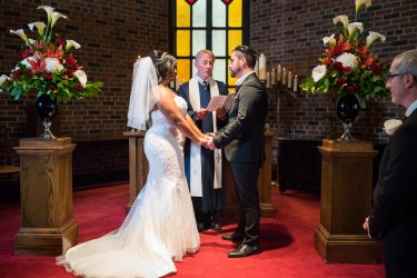 Couple saying their vows at wedding ceremony beside beautiful floral bouquets in vases