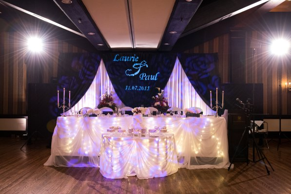 Beautifully draped wedding head table with names projected