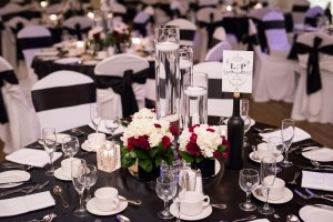 Modern wedding table setting with black ribbon accents and floral centerpieces