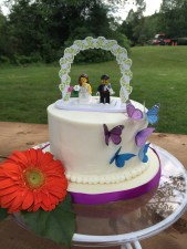 Wedding cake with butterfly accent and lego bride and groom at outdoor wedding