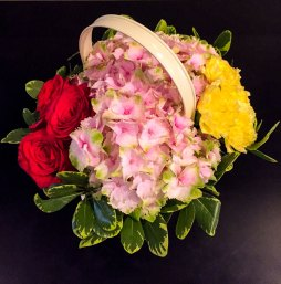 Red, pink and yellow assorted floral in basket centerpiece