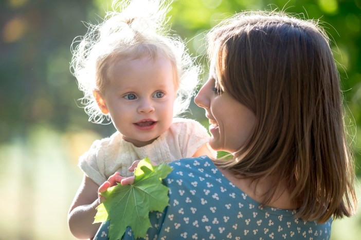 Portrait of happy young mom and adorable blond baby girl, smiling mother holding her little daughter in arms, talking, playing with tree leaf, walking together in park in sunny weather