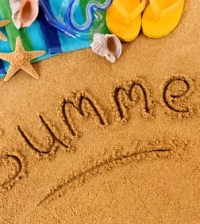 The word Summer written on a sandy beach, with scuba mask, beach towel, starfish and flip flops (studio shot - warm color and directional light are intentional).