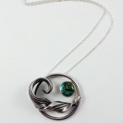 Silver mitsuro wave and a circle of turquoise on a chain.