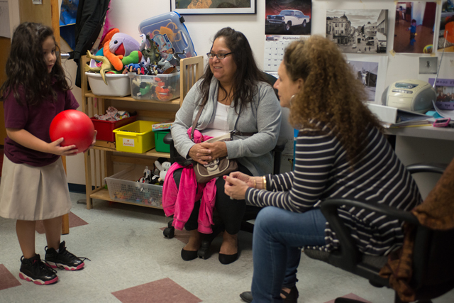 Ana Perez and her daughter Angelina, who received services at Erie Neighborhood House in Chicago with psychologist Elizabeth Yelen (right). (Photo: Julienne Schaer)