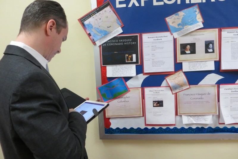 Gregg Korrol, principal of P.S. 101, scans a QR code on a bulletin board and pulls up a video of a fourth-grade class presentation on early sea exploration.