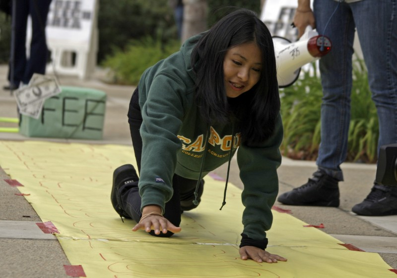 """Mercy Ochoa, a freshman at California State Polytechnic University-Pomona, crawls on all fours - other challenges involved jumping over a fees obstacle, rear, and jumping through hoops - on an inprovised obstacle course that ends in earning a degree - during what a group known as CSU Students for Quality Education call a """"Protest Carnival,"""" mainly in opposition to an increase in student fees, outside a meeting of the trustees of the California State University, at CSUC headquarters in Long Beach, Calif., Wednesday, Nov. 10, 2010."""