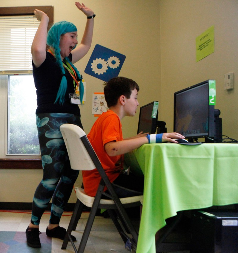 In this Wednesday, June 19, 2013 photo, instructor Melissa Andrews, left, cheers on camper Roger McKee, 9, for finishing a video game while at an iD Tech Camp at the Emory University campus, in Atlanta. So-called coding camps for kids are becoming more popular amid a growing effort to expand access to computer programming and inspire more youths to seek computer science degrees and later careers in technology.