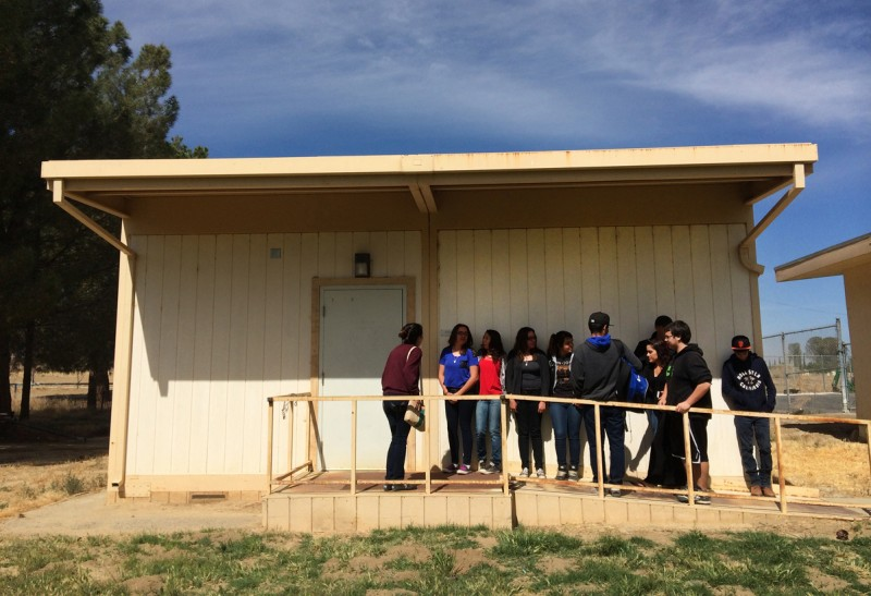 In this April 30, 2015 photo, students line up to take part in new Common Core-aligned standardized tests at the Cuyama Valley High School in New Cuyama, Calif. The Cuyama Joint Unified School District is 60 miles from the nearest city and has Internet connections about one-tenth the minimum speed recommended for the modern U.S. classroom. Across the country, school districts in rural areas and other pockets with low bandwidth are confronting a difficult task of administering new Common Core-aligned standardized tests to students online.