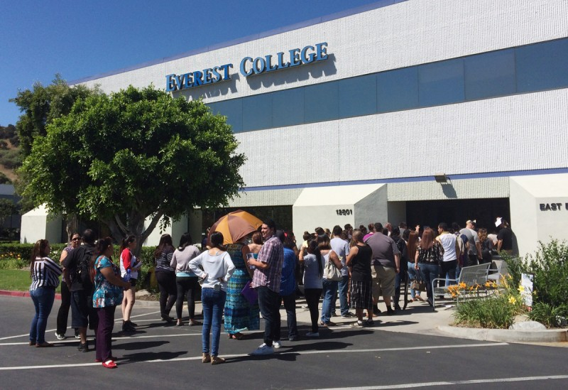 Students wait outside Everest College, Tuesday, April, 28, 2015 in Industry, Calif., hoping to get their transcriptions and information on loan forgiveness and transferring credits to other schools. Corinthian Colleges shut down all of its remaining 28 ground campuses on Monday, April 27, displacing 16,000 students. The shutdown comes less than two weeks after the U.S. Department of Education announcing it was fining the for-profit institution $30 million for misrepresentation.