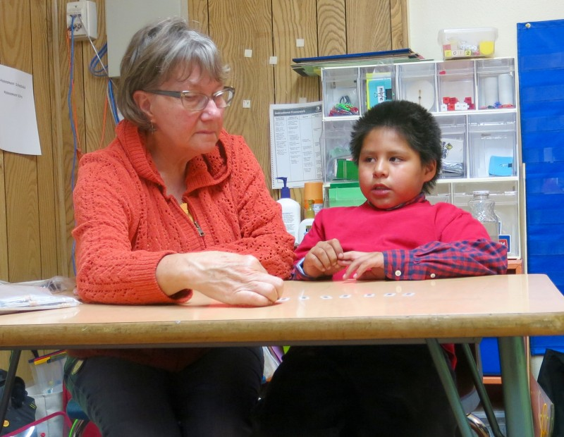 Atsa works on a problem set by Cheryl Williams, the math recovery specialist at Wyoming Indian Elementary School. Williams videotapes her sessions with Atsa. When she reviews the tape, she will look closely at his hands to see if he is counting on his fingers.