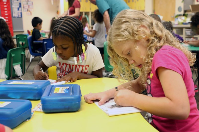 Soon-to-be-kindergarteners Makilah Traylor (l.) and Kimber Runkle color in zebra worksheets highlighting the letter Z.