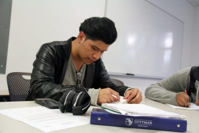 A student at Guttman Community College in New York City reads before the start of a class. Momentum is building to give associate degrees to students who have left community colleges but earned enough credits to get one.