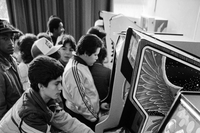 Black and white image of kids in arcade, in the 1980's.