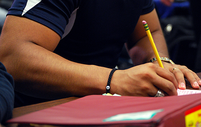 Brandon, 18, takes notes in his English class at Oakland International High School in Oakland California. Brandon arrived in the U.S. a year ago as an unaccompanied minor and did not want his face included in any photos while his deportation hearing is pending. (Photo: Lillian Mongeau)