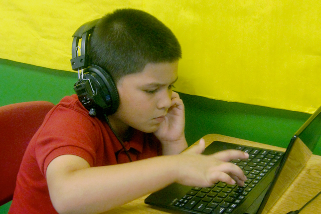 Emaunuel Castillo, a second-grader at KIPP Obras Austin, works on a computer, while other students in his class meet in small groups with a teacher. (Gail Robinson)