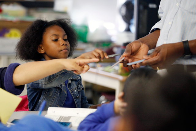 Nydresha, performing a science experiment with her sixth-grade classmates, wants to do well in school but sometimes gets lured into chatting with friends during class time. (Amanda Brown / NJ Spotlight)