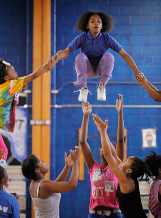 Nydresha begins a stunt called the yo-yo, requiring her to somersault in midair. It is so difficult that none of the other 18 teams competing in Newark's elementary cheerleading tournament would even attempt it. (Amanda Brown / NJ Spotlight)