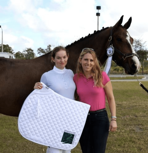 Photo: Chloe Hatch (left) and trainer Heidi Degele pose with Hatch's  mount Prince Paradiso and their prize, an embroidered saddlepad from Everglades Dressage. (Photo courtesy of JRPR—no photo  credit necessary)