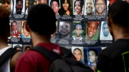 People look over a pictures of people who have been killed by police officers in recent years during a gathering to mark the one year anniversary of the death of Michael Brown in Union Square in New York, New York, USA, 09 August 2015. Brown was killed by police officer Darren Wilson in Ferguson, Missouri, and his death set off nationwide protest against police brutality. EPA/JUSTIN LANE