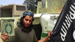 A framegrab made from an undated video released by the jihadist group calling itself Islamic State (IS) allegedly showing Abdelhamid Abaaoud posing with a Koran and the ISIS flag at an undisclosed location. EPA