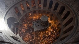FILE PHOTO: An image taken with a wide angle lens of Orthodox Christian worshippers holding candles at the Tomb of Christ as the miracle of the Holy Fire occurs in the Church of the Holy Sepulchre, Jerusalem, Israel, 30 April 2016. EPA, ABIR SULTAN