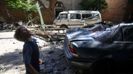 FILE PHOTO. A Syrian child stands next to damaged vehicles and buildings in Syria. EPA, Mohammed Badra