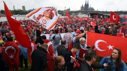 FILE PHOTO. Supporters  wave Turkish flags at the start of a pro-Erdogan rally in Cologne, Germany. EPA/HENNING KAISER