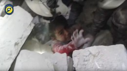 A handout frame grab from video footage released on 17 November 2016 by the Syrian Civil Defense, also known as the White Helmets, showing rescuers trying to pull out a child trapped under the rubbles of a building at Maadi neighborhood, Aleppo, Syria. No further details were given on the incident. According to monitors and rescue groups, airstrikes and artillery fire, reportedly by forces loyal to the Syrian government, continued over the rebel-held neighborhoods of Aleppo during the past five days, killing dozens and damaging some of the few remaining hospitals in the city. EPA/WHITE HELMETS / HANDOUT ATTENTION EDITORS: PICTURE CONTAINS GRAPHIC CONTENT. BEST QUALITY AVAILABLE HANDOUT EDITORIAL USE ONLY/NO SALES