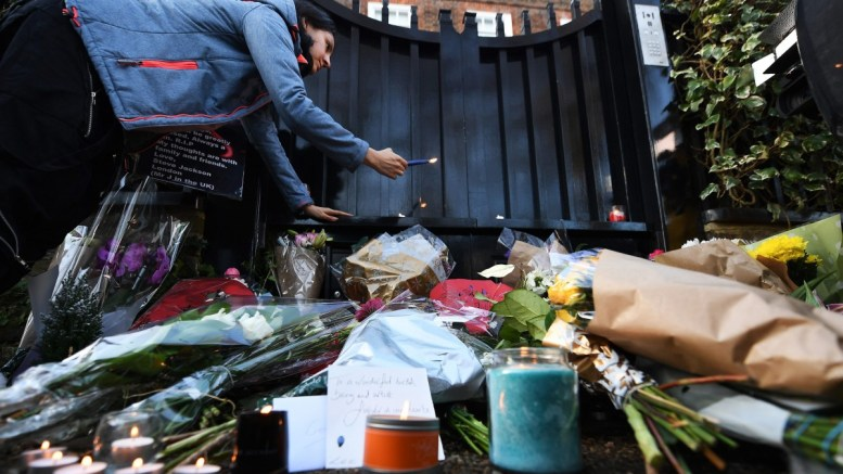 A woman lights a candle as flowers and tributes lay outside the home of late British singer-songwriter George Michael in London, Britain, 26 December 2016. Michael died at his home in Goring, Oxfordshire on 25 December. He was 53. EPA, ANDY RAIN