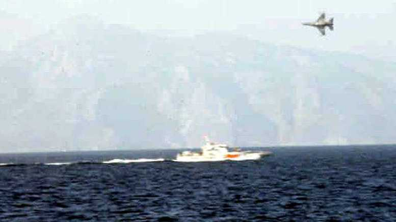 File PHOTO: A Turkish Coastguard vessel is overflown by a Greek military plane 29 January in the Agean Sea. Reportedly some Greek soldiers were stationed on the island of Imia on Monday, following an incident over the weekend, which caused a diplomatic row between Turkey and Greece. Turkish journalists on Saturday had removed a Greek flag from the Imia island and had hoisted a Turkish one at its place. Following an official protest to Turkey, a Greek Navy vessel on Sunday was despatched to rehoist the Greek flag on the deserted island. Photo via AΠΕ-ΜΠΕ via Turkish Navy. EDS note: best quality available