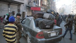 An armed person stands next to a car packed with baggage as civilians crowd a street in the eastern part of Aleppo, Syria, 15 December 2016 (issued 16 December 2016). Evacuation of civilians from the rebel-held parts of Aleppo was suspended according to news reports on 16 December 2016. Aleppo's residents have been under siege for weeks and have suffered bombardment, together with chronic food and fuel shortages. EPA/GHITH SY