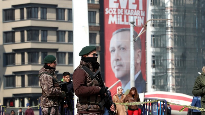 Members of Turkish Special forces guard in front of a giant picture of Turkish President Recep Tayyip Erdogan reading, 'Vote Yes, only public can speak and make decision', at the Taksim Square in Istanbul. EPA, TOLGA BOZOGLU