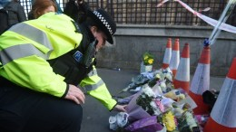 A police woman lays flowers by the Houses of Parliament following the 22 March incidents in central London, Britain, 23 March 2017. Scotland Yard said on 23 March 2017 that police have made seven arrests in raids carried out over night after the terror attack in the Westminster Palace grounds and on Westminster Bridge on 22 March 2017 leaving at least four people dead, including the attacker, and 29 people injured. EPA/FACUNDO ARRIZABALAGA