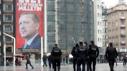People walk in front of a giant poster of Turkish President Recep Tayyip Erdogan. EPA/TOLGA BOZOGLU