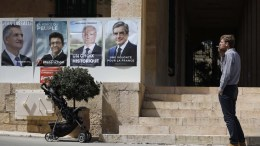 A man smoke a cigarette as he stands next to posters of French presidential election candidate before casting his vote for the 2017 French presidential elections at the French Consulate in Jerusalem, Israel, 23 April 2017. EPA, ABIR SULTAN