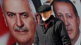 A man walks past a poster with Turkish President Recep Tayyip Erdogan (R) and Turkish Prime Minister Binali Yildirim (L) in Istanbul, Turkey, 14 April 2017. EPA, SEDAT SUNA