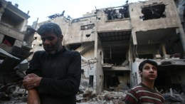 FILE PHOTO. An injured man stands with his son in front of their destroyed house in Syria. EPA/Mohammed Badra